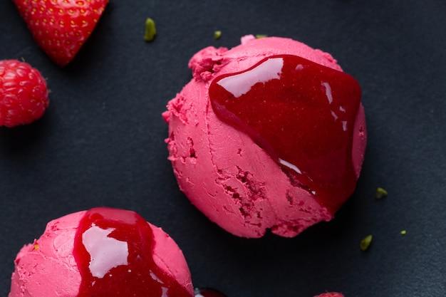 Colheres de sorvete de morango com molho de morango servidas no prato com frutas e pistácios. vista do topo.