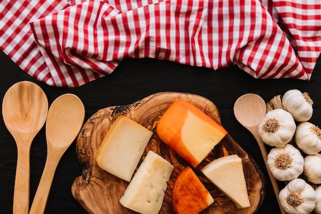 Colheres e guardanapo perto de queijo e alho