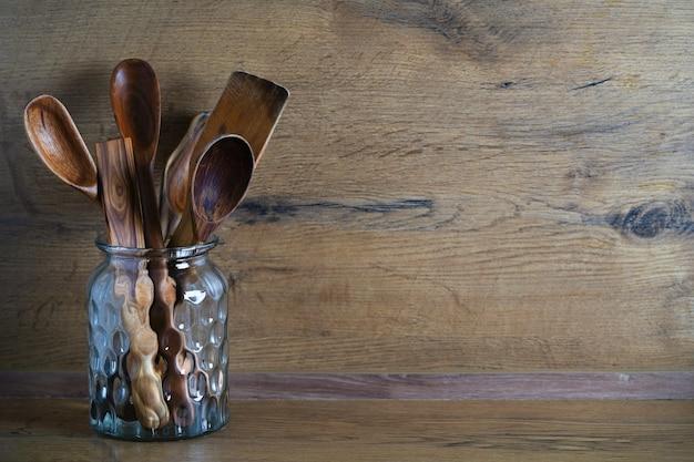 Colheres e outros utensílios de madeira em uma jarra sobre uma mesa de madeira. foto de alta qualidade