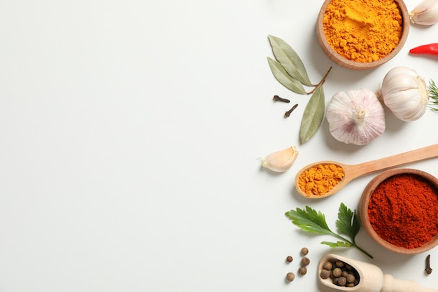Colheres e tigelas com diferentes especiarias e ingredientes em branco, espaço para texto
