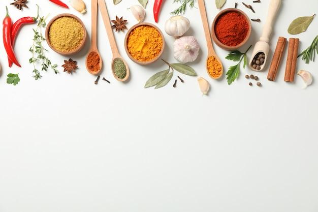 Colheres e tigelas com diferentes especiarias e ingredientes em fundo branco, espaço para texto