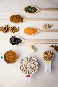 Colheres e xícaras de legumes e sementes na mesa de madeira
