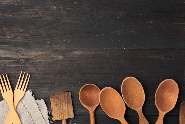 Colheres, garfos e espátulas de madeira vazias em um est de madeira marrom