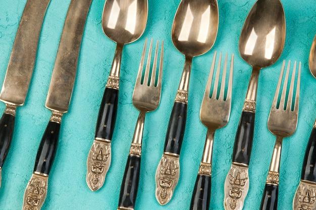 Colheres, garfos e facas de latão sobre fundo de concreto.
