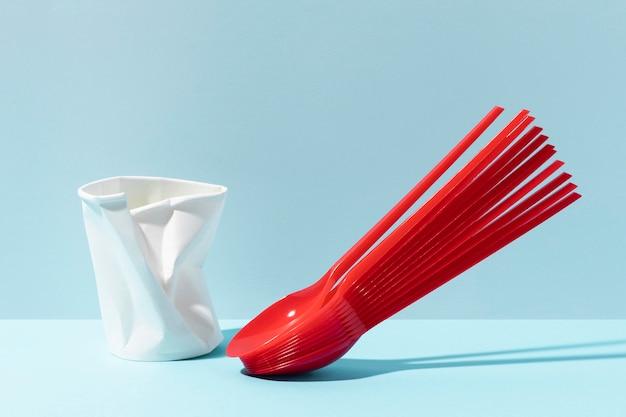 Colheres pequenas vermelhas e copo de plástico amassado