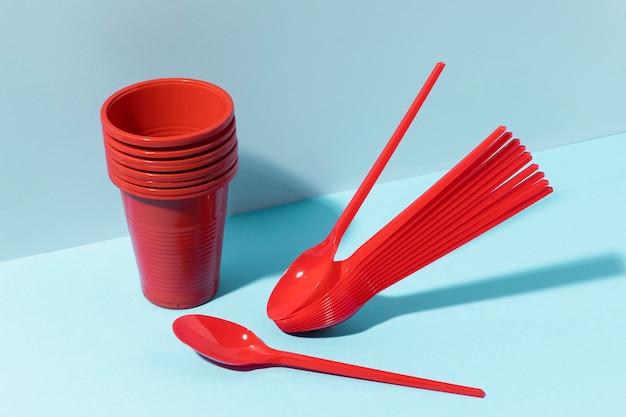 Colheres vermelhas pequenas e copos de plástico