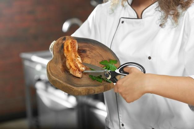Colhido perto acima de um cozinheiro chefe fêmea que usa a tesoura ao trabalhar em sua cozinha que corta o frango grelhado que prepara o prato delicioso.