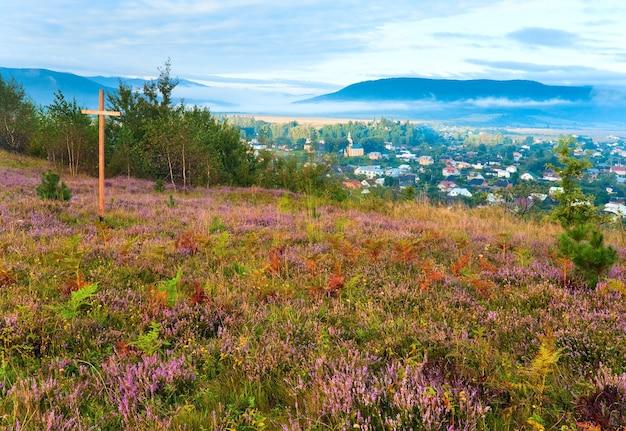 Colina de flores de urze de verão, vista do país pela manhã nublada por trás e cruzes de madeira (oblast de lviv, ucrânia).
