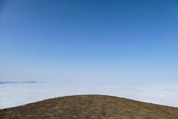 Colina de terra com fundo de nuvens e céu azul