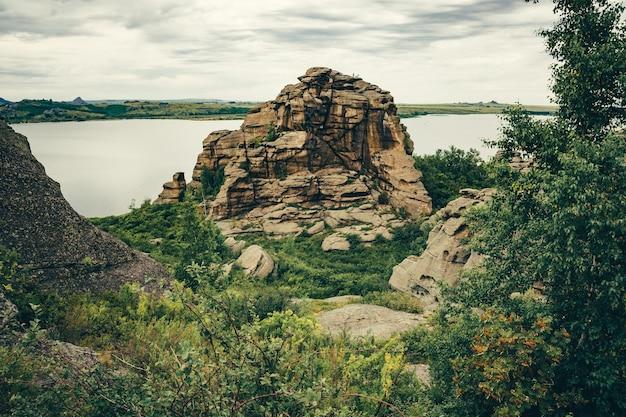 Colina rochosa entre vegetação e lago