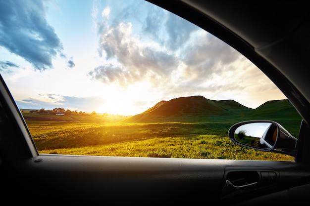 Colina verde ao pôr do sol de dentro de um carro