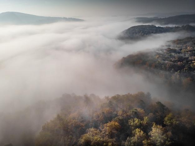 Colinas arborizadas, rodeadas de nevoeiro sob um céu nublado