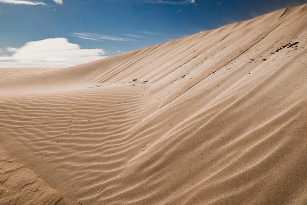 Colinas arenosas em uma área deserta com rastros deixados pelo vento