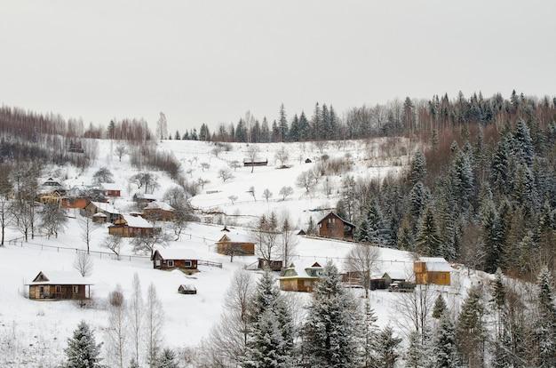 Colinas cobertas de neve, florestas e casas à distância.