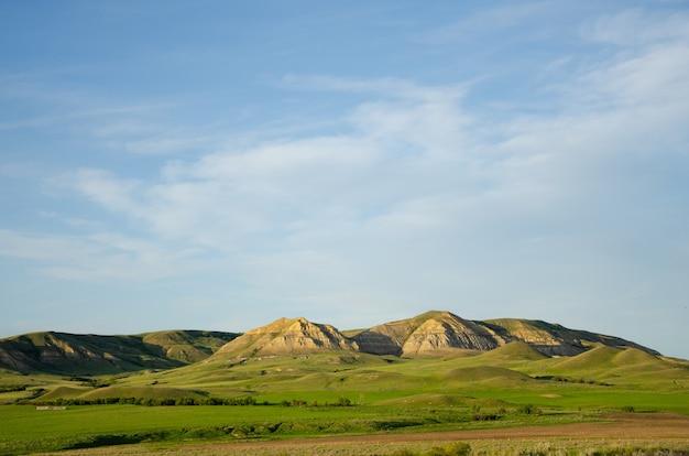 Colinas e montanhas brilhando sob o céu azul nublado
