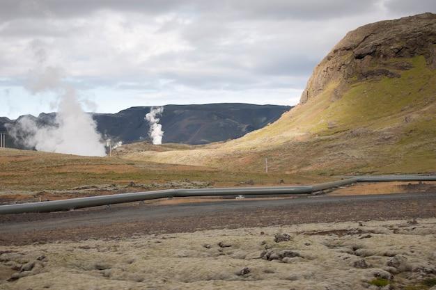 Colinas e montanhas escarpadas com vapor subindo e um pipline de gás ao longo da estrada