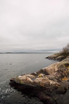 Colinas rochosas perto do mar com um céu nublado