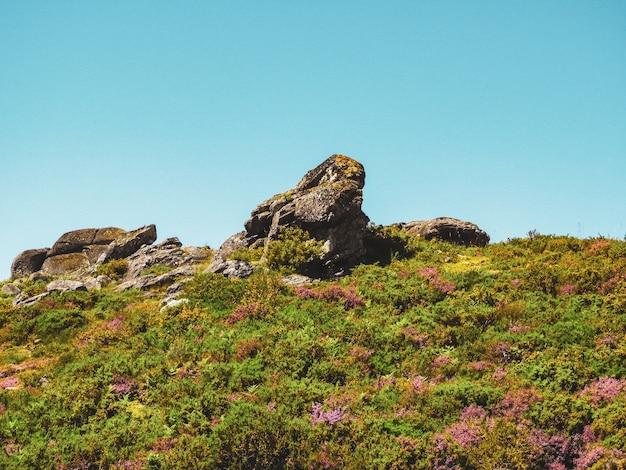 Colinas verdes e grandes rochas sob o céu nublado