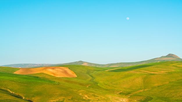 Colinas verdes e paisagem de céu azul