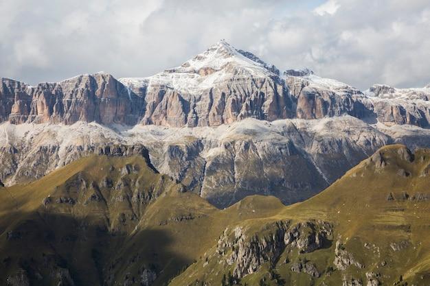 Colinas verdes e rochas nevadas do grupo de montanhas sella. vista de marmolada, dolomitas, itália