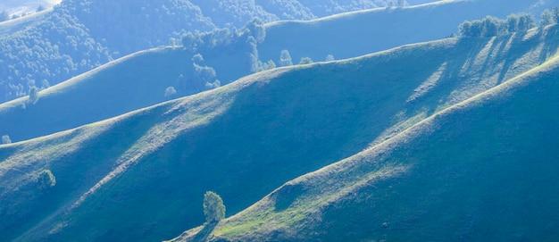 Colinas verdes, prados e encostas de montanha