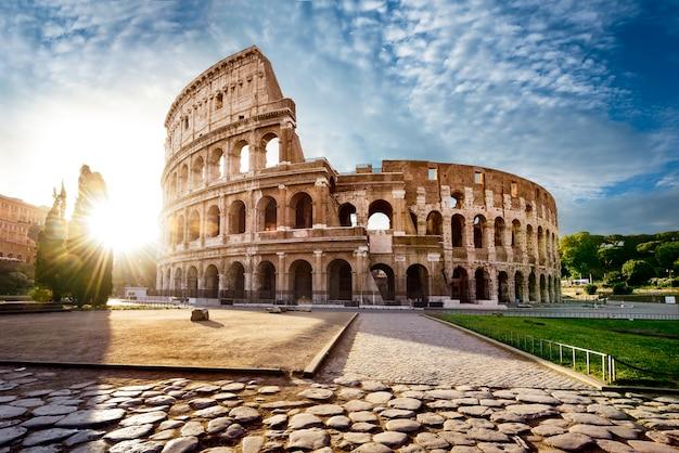 Coliseu, em roma e sol da manhã, itália