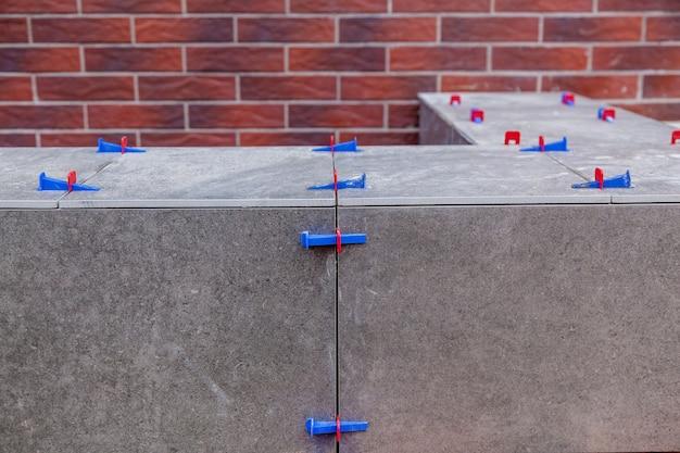 Colocação de ladrilhos cerâmicos com sistema de nivelamento. novas ferramentas de alinhamento de ladrilhos