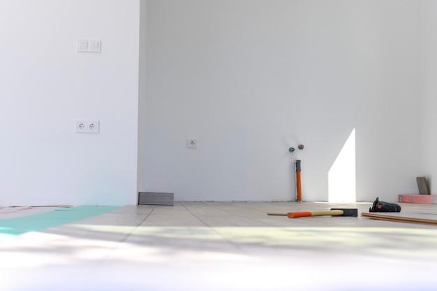 Colocação de piso laminado em acabamento de sala branca vazia de redecoração de casas e apartamentos no