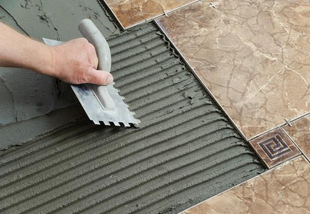 Colocação de telhas cerâmicas. espátula adesiva em um piso de concreto como preparação para o assentamento de ladrilhos brancos.