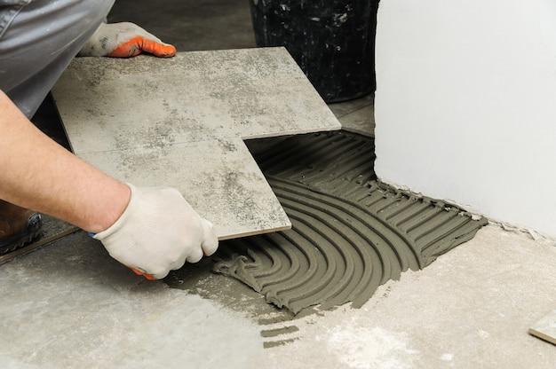 Colocação de telhas cerâmicas. trabalhador colocando ladrilho de cerâmica em posição sobre o adesivo.