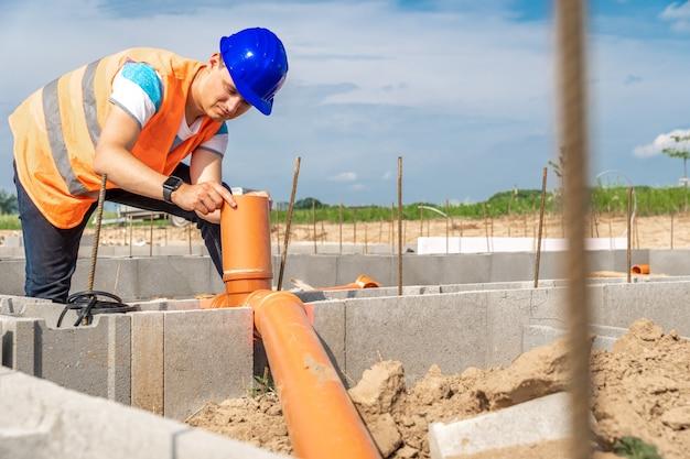 Colocação de tubos de plástico na fundação do edifício.