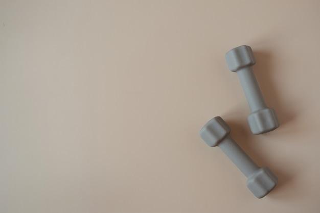 Colocação estética e criativa de halteres para ioga, condicionamento físico e treinamento físico em bege neutro
