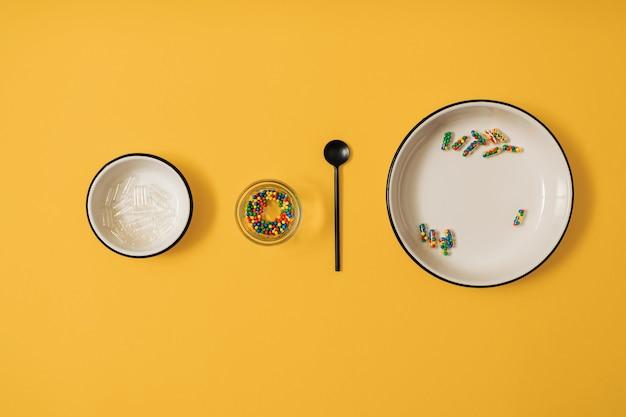 Colocação plana colorida vibrante de cápsulas de comprimido de remédio cheias de açúcar doce granulado sobre fundo amarelo. conceito criativo de uso de medicamento de overdose e dependência de suplemento alimentar.