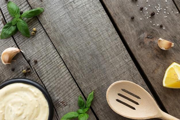 Colocação plana conceitual. fazer molho de creme de alho ou molho de queijo de cozinha, maionese, mostarda, alimentos e temperos na mesa de madeira.