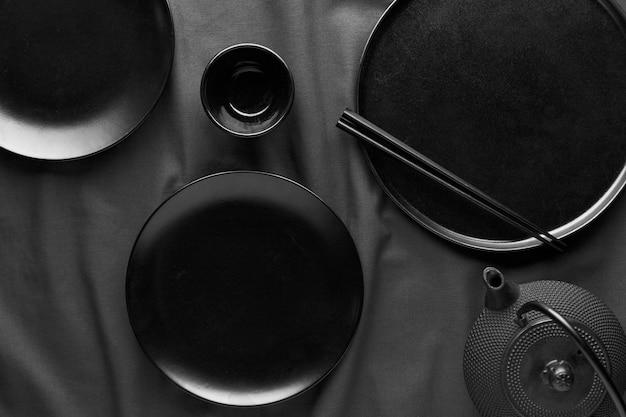 Colocação plana de pratos escuros e pauzinhos