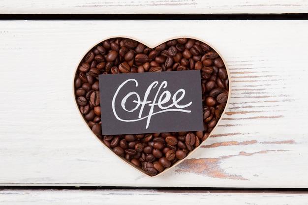 Colocação plana do café do coração. conceito de amor do café. madeira branca na superfície.
