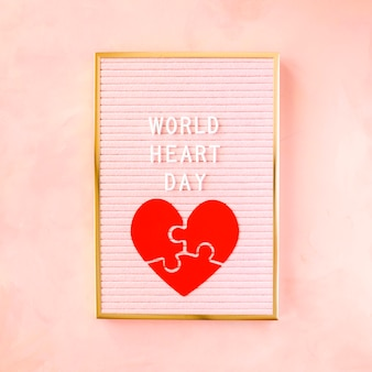 Colocação plana do coração de papel para o dia mundial do coração no quadro
