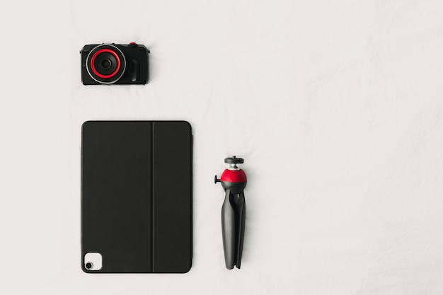 Colocação plana dos equipamentos digitais do tablet e tripé da câmera