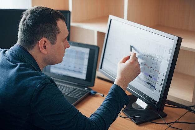 Colocando atenção em cada momento. o examinador de polígrafo trabalha no escritório com seu equipamento detector de mentiras