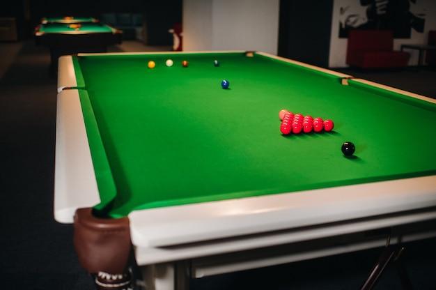 Colocando bolas de sinuca em uma mesa de bilhar verde.