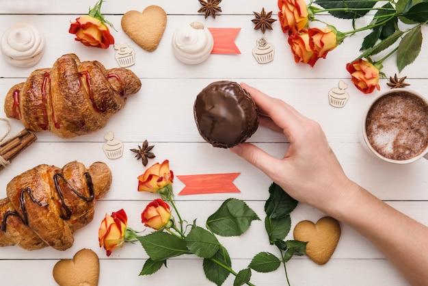 Colocando bolinho de chocolate caseiro na mesa de madeira decorada com croissants e flores para o aniversário do dia dos namorados