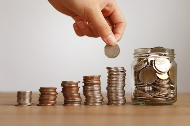 Colocando dinheiro em uma pilha, economizando dinheiro