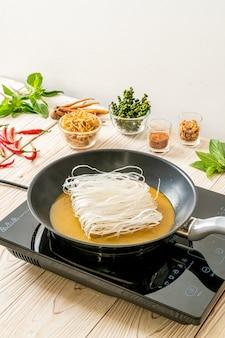 Colocando macarrão na panela com molho pronto para fritar