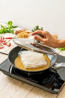 Colocando macarrão na panela com molho