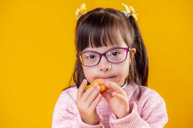 Colocando o chip dentro. criança incomum de cabelo curto com grandes olhos castanhos comendo lanches não saudáveis enquanto fica na parede laranja