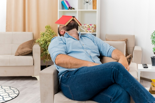 Colocando o homem eslavo adulto sentado na poltrona segurando um livro no rosto dentro da sala de estar