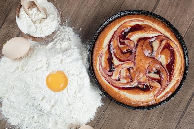 Colocando os ingredientes em uma mesa de madeira e fazendo uma torta
