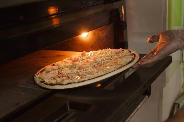 Colocando pizza de frutos do mar no forno preparando pizza tradicional italiana em pizzaria.