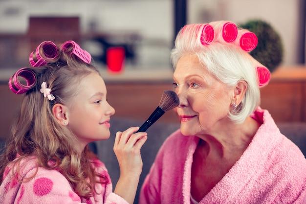 Colocando pó facial. linda garota segurando uma escova de cosméticos e passando pó facial no rosto da vovó