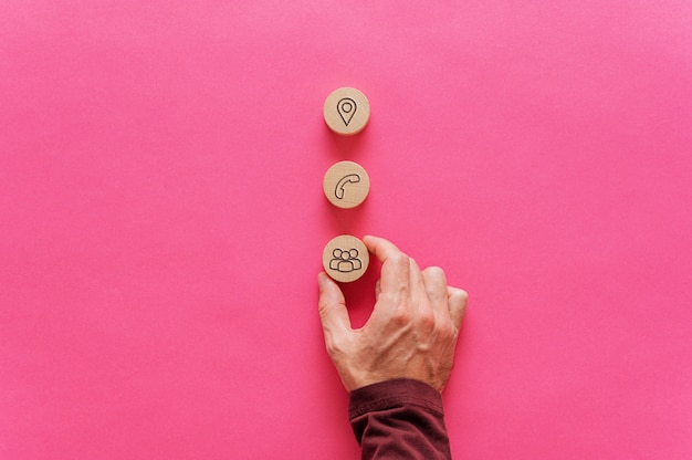 Colocando três círculos de corte de madeira com ícones de contato e informações sobre eles